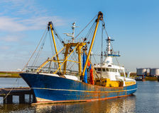 Rusty Dutch trawler moored at a wooden jetty Royalty Free Stock Images