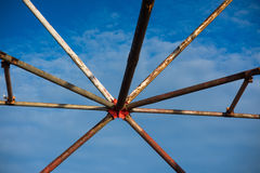 Rusty electrical tower supports as an art object in the background of blue sky Stock Image