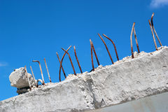 Rusty ends of steel rebars sticking out of concrete block. Rusty ends of steel reinforcing bars sticking out of demolished concrete block on blue sky background Stock Photos
