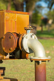Rusty energy supply pipeline pump outdoors. Close up rustic colored pump pipeline with elbow pipe and old valve for residential energy supply, blurred background Stock Photography
