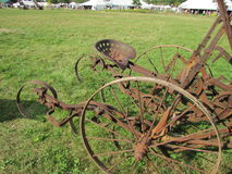 Rusty farm equipment. This vintage tractor serves to remind of the past for farmers and visitors to a country fair Stock Images