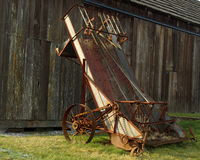 Rusty farm machinery. Rusty antique farm machinery against barn wall Royalty Free Stock Photography
