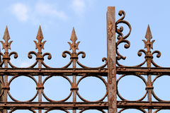 Rusty Fence. Rusty iron fence detail isolated on light blur sky stock photography