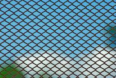 Rusty fence on blue sky. Chain link rusty fence on a blue sky background Stock Image