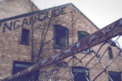Rusty fence in front of old brick building stock photography