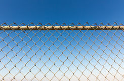 Rusty fence rabitz on the background of sky. Royalty Free Stock Photography