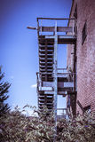 Rusty fire escape of derelict red brick building Royalty Free Stock Photos