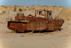 Rusty fishing boat lying in the sand. Rusty ship lying in the sand at the former Soviet Aral Sea port of Moynaq in Uzbekistan Royalty Free Stock Photography