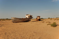 Rusty fishing boats lying in the sand. Rusty ship lying in the sand at the former Soviet Aral Sea port of Moynaq in Uzbekistan Stock Image