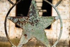 Rusty five-pointed star in an iron fence of a deserted industrial site stock photo