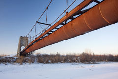 Rusty flume suspended over a river Royalty Free Stock Photo