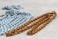 A rusty and a fresh painted anchor chain. Lying on the ground Stock Photo