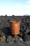 The rusty garbage bin on the volcanic land. Stock Photography
