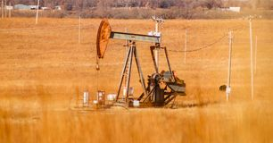 Oil pumpjack in an orange winter field full of electric poles with blurred grass in the foreground. Rusty gas - oil pumpjack in an orange winter field full of Stock Photography
