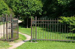Rusty gate at an old estate. An open 19th century fence / gate leads us into the property along a winding path Royalty Free Stock Photography