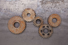 Rusty Gears. A group of five rusty gears linked together over a grungy steel background Stock Images