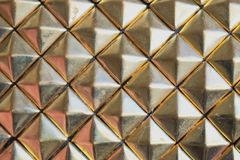 Rusty golden diamonts pattern. Plastic background royalty free stock photography