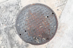 Rusty, grunge manhole cover NOT isolated Royalty Free Stock Image