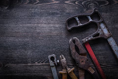Rusty hacksaw nippers pliers on wooden board construction concep Royalty Free Stock Photography