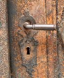 Rusty handle of an old wooden door Stock Images