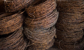 The rusty hanks of an old barbed wire lying in military warehous Stock Image