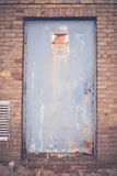 Rusty high voltage warning sign at a old metal door Royalty Free Stock Images