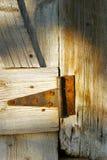 Rusty hinge. Rusting metal hinge on a weathered wood door royalty free stock photography