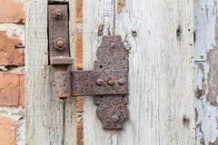 Rusty hinge on old wooden door. Royalty Free Stock Photo