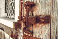 Rusty Hook and eye fastener on rustic shutter.  stock photo