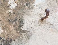 Rusty hook to the right on plastered wall Royalty Free Stock Photos