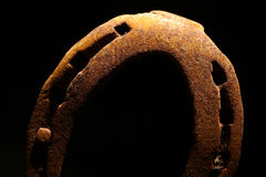 Rusty horse shoe. Color shot of a rusty horse shoe on a dark background Stock Image
