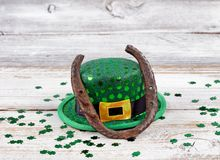 Rusty horseshoe with hat and clovers for St Patrick day. Close up view of a rusty horseshoe resting on hat for St Patrick day with shiny clovers on weathered Royalty Free Stock Photo