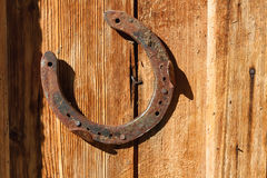 Rusty horseshoe on old wooden background. Outdoors image on a sunny day Stock Photography