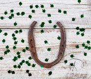 Rusty horseshoe with shinny clovers for St Patrick Day. Close up view of a rusty horseshoe for St Patrick day with shiny clovers on weathered white wooden boards Stock Photos