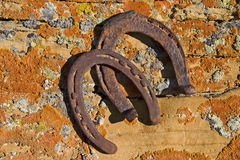 Rusty horseshoes on lichen covered sandstone Royalty Free Stock Photography