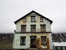 Rusty House Isafjordur Iceland. Rusty green house on a street in front of a low lying cloud and snow striped mountain in Isafjordur Iceland Stock Image