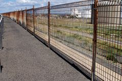 Rusty fence. Perspective shot of rusty fence line with petrol tanks in bankground. Copyspace Royalty Free Stock Photo