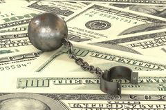 Rusty iron ball and chain connected to open cuff lying on dollar banknotes background. 3d illustration: rusty iron ball and chain connected to open cuff lying Royalty Free Stock Photography