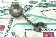 Rusty iron ball and chain connected to open cuff lying on rouble banknotes background. 3d illustration: rusty iron ball and chain connected to open cuff lying on Royalty Free Stock Photo