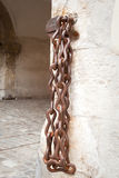 Rusty iron chain on brick wall of historic building Stock Image