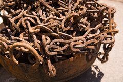 Rusty iron chain in cankered bucket, outdoor under sunlight stock photography