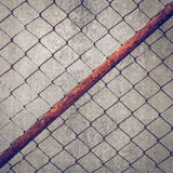 Rusty iron chain wire fence on cement wall Stock Images