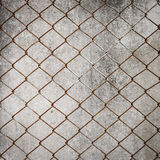 Rusty iron chain wire fence on cement wall Stock Photos