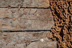 Rusty iron chain on a wooden texture background Stock Photography