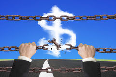 Rusty iron chains broken off by hands with dollar sign. Shape white clouds on sky asphalt road background Royalty Free Stock Photo