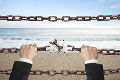 Rusty iron chains broken off by hands with sky sea Stock Photography