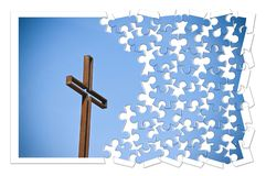 Rusty iron cross against a blue background - Rebuild our faith - Christian cross concept image in jigsaw puzzle shape.  stock photos