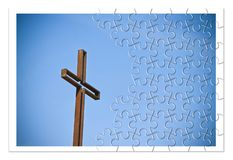 Rusty iron cross against a blue background - Rebuild our faith. Christian cross concept image in jigsaw puzzle shape royalty free stock image