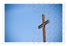 Rusty iron cross against a blue background - Rebuild our faith. Christian cross concept image in jigsaw puzzle shape royalty free stock photos