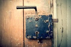 Rusty iron doorknob on wooden door Stock Photo